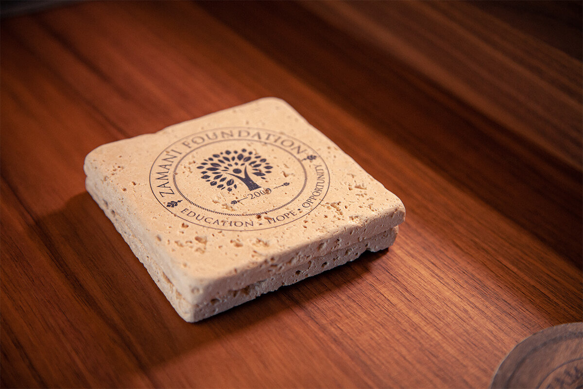 Zamani Foundation logo on square cork cup holder